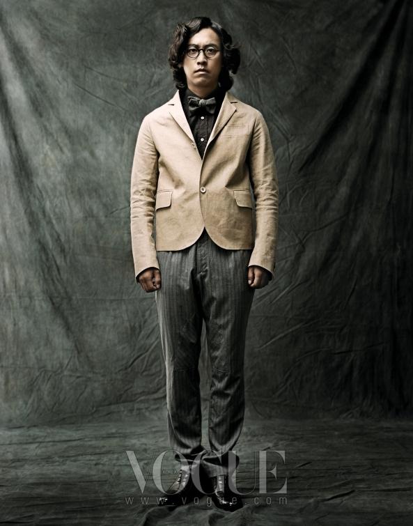 이너로 매치한 블랙 셔츠는 돌체 앤 가바나(Dolce&Gabbana), 빳빳한 소재가 돋보이는 베이지 쇼트 재킷과 그레이 스트라이프 팬츠는홍승완(Sweet Revenge), 다크 그레이 보타이는 란스미어(Lansmere), 브라운 라운드 프레임 안경은 프랑소와 핀톤(Francois Pinton at Dari International), 브라운 슈즈는 소다 옴므(Soda Homme).