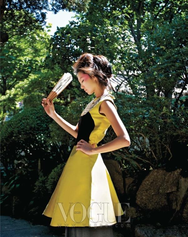 빳빳한 실크 소재로 만들어져 볼륨이 살아 있는 옐로 컬러의 드레스는 이브 생 로랑, 골드 깃털 장식의 네크리스는 샤넬(Chanel), 손에 든 부채는 소서노 한복.