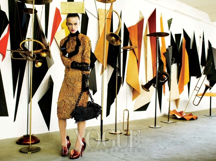 Symphony Space 아티스트 카티야 스트런츠의 설치 작품 앞에서 포즈를 취한 키이라 나이틀리. 브론즈 색상의 기퓌르 레이스 드레스와 블랙 목 장식과 플렉시 글라스 소재의 목걸이, 레이스 장식의 백과 러플 장식 슈즈는 모두 프라다(Prada).