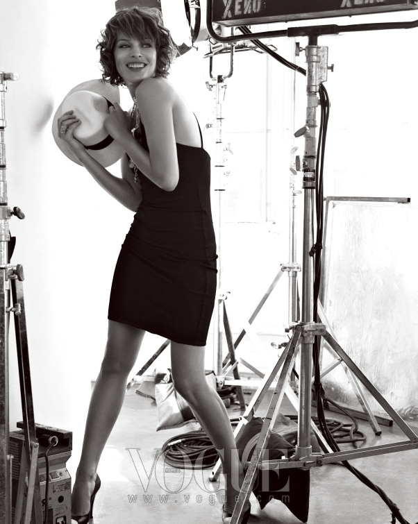 밀라의 탄력 있는 몸매가 잘 드러나는, 타이트한 저지 소재로 만들어진 심플한 블랙 슬립 원피스와 라피아 햇까지 모두 랄프 로렌 컬렉션.
