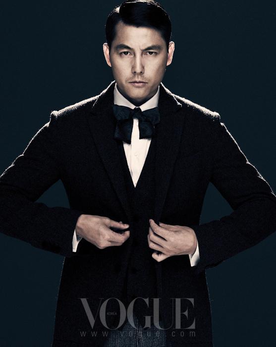 화이트 셔츠와 다크 그레이 베스트, 모직 소재의 싱글 재킷, 체크 패턴 팬츠, 블랙 보 타이는 모두 돌체앤가바나(Dolce&Gabbana).