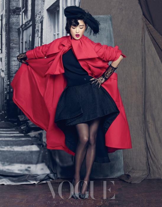 리본 칼라의 빨강 오버 사이즈 코트 또한 무슈 디올의 유산 중 하나. 안에는 검정 민소매 니트와 언밸런스한 디자인의 볼륨 스커트를 입었다.