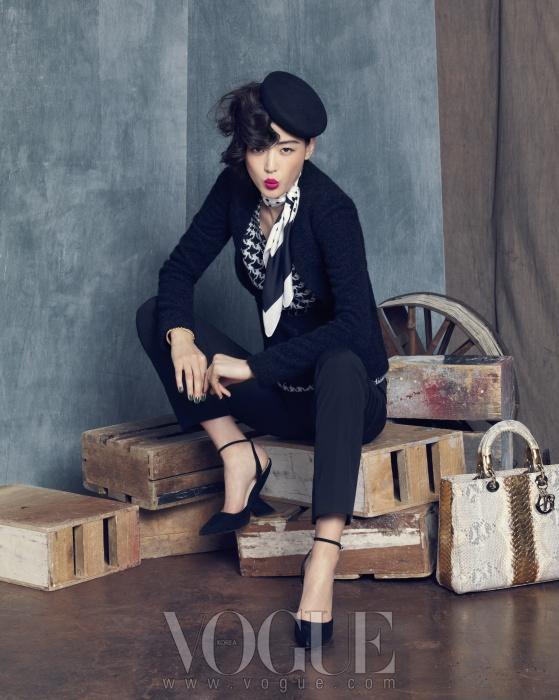 하운드투스 체크 패턴의 니트 톱 위엔 꾸뛰르적 터치가 가미된 심플한 검정 트위드 재킷과 팬츠를 매치했다. 의상과 슈즈, 백, 액세서리는 모두 디올(Dior).