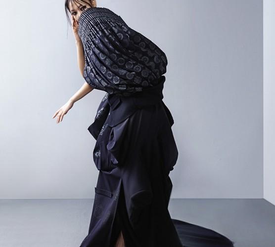 전통 문양이 프린트된 플리츠 디테일이 풍성하게 장식된 아방가르드한 디자인의 롱 드레스는 구호(Kuho, 2013), 자카드 장식 힐은 게스(Guess).