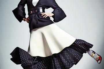 화이트 민소매 터틀넥과 미디 스커트는 셀린(Céline), 발목까지 오는 도트 무늬 풀 스커트와 넓은 가죽 벨트, 줄무늬 스타킹은 모두 미우미우(Miu Miu), 소매 끝이 독특한 재킷과골드 스트랩 펌프스는 프라다(Prada).