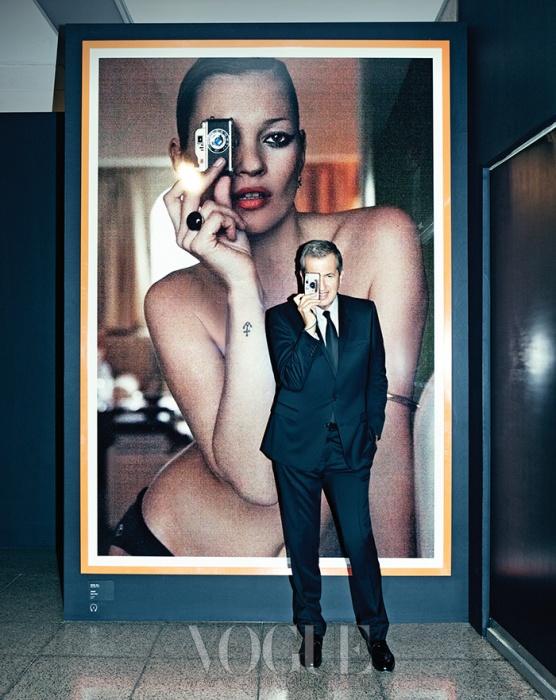 전시장 입구에 전시된, 자신이 촬영한 케이트 모스의 포트레이트 사진 앞에서 똑같은 포즈를 취한 마리오 테스티노.