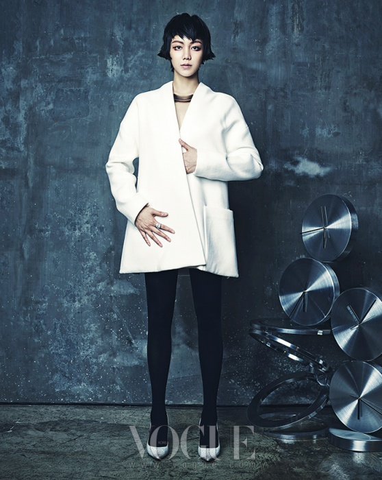 A라인 실루엣의 울 소재 재킷은 캘빈 클라인 컬렉션(Calvin Klein Collection), 목걸이는 스와로브스키(Swarovski), 반지는 누이(Neu), 화이트 펌프스는 지미 추(Jimmy Choo). 유리와 스틸 장식의 모던한 테이블은 까레(Kare).