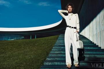 실크 소재 하이넥 블라우스와 흰색 와이드 팬츠, 검정 벨트와 슬리퍼는 셀린(Céline), 앤티크 코인 모티브의 핑크 골드 목걸이와 왼손의 옐로 골드 뱅글은 불가리(Bvlgari), 체인 스트랩 숄더백은 샤넬(Chanel).
