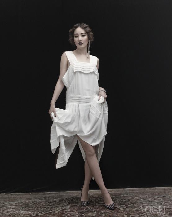 20년대 스타일의 화이트 플리츠 드레스, 크리스털 길게 늘어진 귀고리는 쟈뎅 드 슈에뜨(Jardin de Chouette), 하운드투스 체크 패턴의 펌프스는 디올(Dior), 진주 장식 뱅글은 샤넬(Chanel).