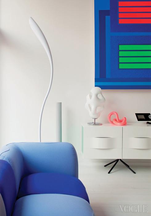 하늘색 소파는 카림 라시드가 디자인한 Kivas 소파로 Valdichienti 제품. 흰색 곡선의 램프는 Doris로 Artemide 제품이며, 캐비닛은 BoConcept의 Ottawa 컬렉션. 핑크빛 화병은 Bitossi Ceramiche, 화이트 Bokka 램프는 Kundalini. 푸른색 회화 작품은 Peter Halley.