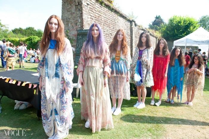 워렌 자매와 스패니어 자매가 벽이 둘러진 정원에서 무대에 올라가기 위해 준비 중. 그들은 모두 잔드라 로즈 차림이다. 한편 줄 맨 끝에 서있는 모델은 잔드라에게 영감 얻은 케이트 모스 for 톱숍(Kate Moss for Topshop)을 입었다. ⓒ Fiona Campbell