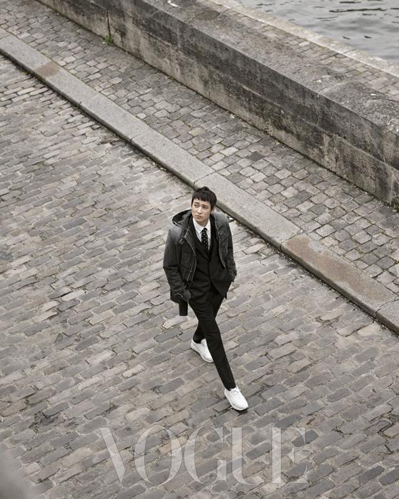 클래식한 핀스트라이프 패턴 스리피스 팬츠 수트에 유니크한 도트 넥타이와 캐주얼한 스니커즈를 매치했다. 데님 소재로 된 후드 더플 코트는 이번 시즌 디올 옴므의 키 아이템이다.