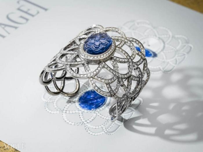 손으로 조각한 블루 사파이어 한 개와 601개 브릴리언트 컷의 다이아몬드, 그리고 피아제 56P 쿼츠 무브먼트가 세팅된 18 K 화이트 골드 비밀 커프 시계가 본래의 디자인 위에 놓여있다. ⓒ Piaget