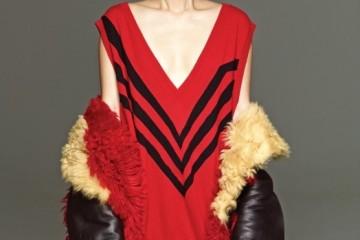 시원하게 파인 빨강 브이넥니트 스웨터와 검정 A라인 스커트,빨강과 노랑으로 염색된 무톤 코트는모두 프라다(Prada).