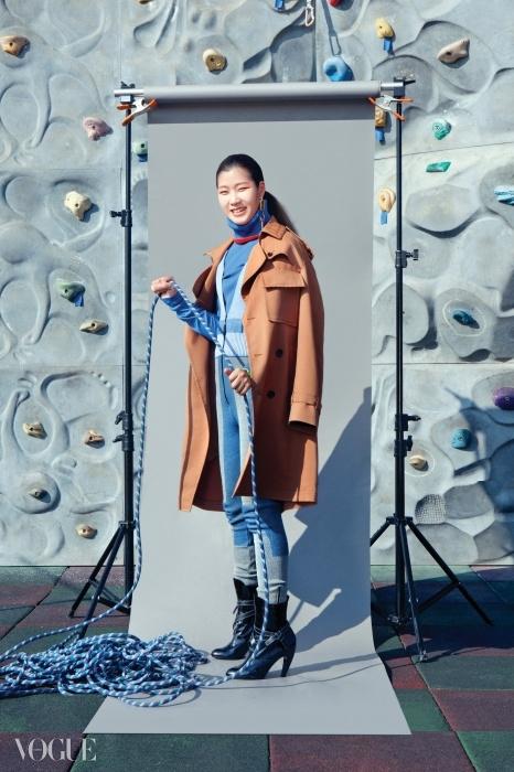 하늘색 터틀넥과 컬러 블록 보디수트, 어깨에 걸친 트렌치코트,앵클 부츠, 골드 싱글 귀고리는 모두루이 비통(Louis Vuitton),주홍색 넥워머는 디올(Dior).
