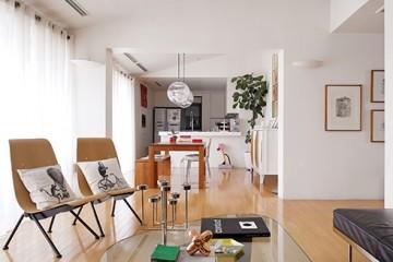 천장을 높게 개조해 탁 트인 느낌이 드는거실. 통창으로 환한 햇살이 들어온다.깔끔한 디자인의 원목 가구는모두 60년대 이전 건축가들의 작품.