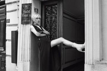 하이 네크라인이 특징인 민소매 레이스 톱과깊은 슬릿이 가미된 검정 실크 드레스.