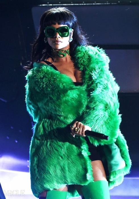 리한나가 70년대 풍 초록색 베르사체 퍼 코트를 입고 무대에서 공연을 하고 있다.ⓒ Getty Images