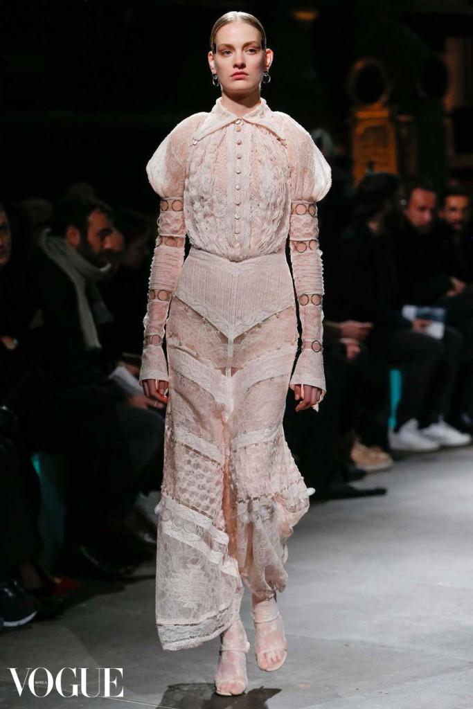 오로지 레이스 밴드로만 만들어진 드레스를 입고 런웨이에 선 모델 수니바 바테비크. 소매 안쪽에는 깃털 장식이 들어가 있으며, 레이스 피스들은 작은 메탈 링 아플리케 장식으로 연결되어 있다. 함께 입은 점프수트 또한 레이스로 만들어졌다.