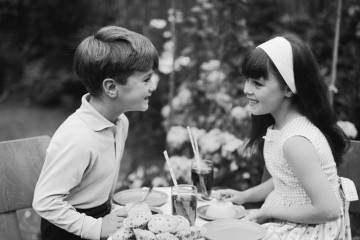 19th July 1966:  A boy and a girl share a teatime snack of cakes and soft drinks.  (Photo by Chaloner Woods/Getty Images)