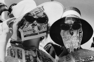 31st December 1963:  Two girls protect themselves from the fierce glare of the sun with newspapers, during the Davis Cup Challenge Tennis Championships, in Adelaide.  (Photo by Keystone/Getty Images)