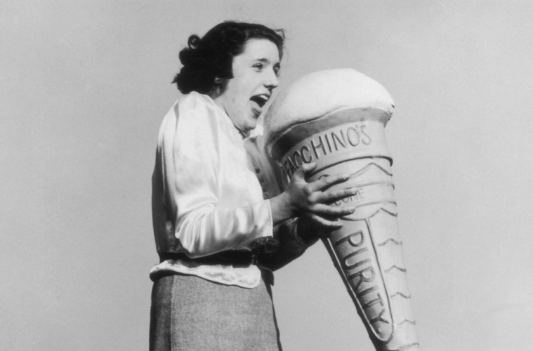 21st May 1938:  A woman holding a giant model of an ice cream cone on the seaside promenade at Morecambe, Lancashire.  (Photo by Fox Photos/Getty Images)