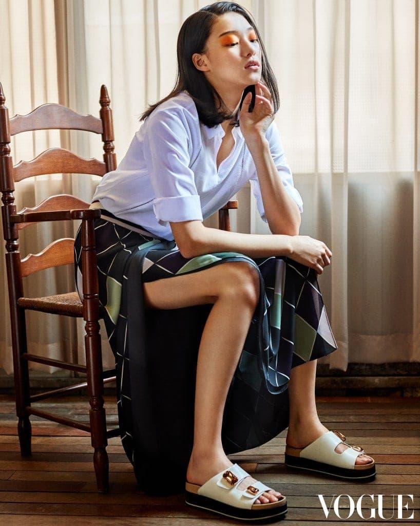 코튼 소재의 미니멀한 화이트 셔츠, 아가일 체크 패턴의 롱 슬릿 스커트, 스톤 장식의 링키 샌들. 모두 구호(Kuho) 제품.