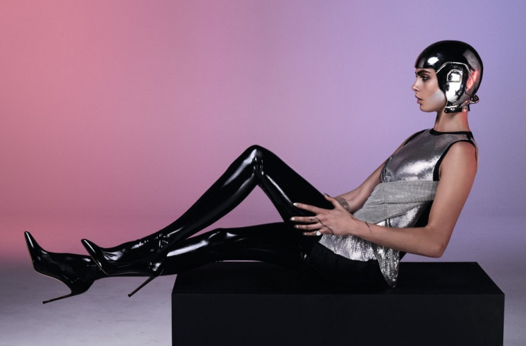 cover feature, Cara Delevingne actress model wearing Theirry Mugler Archival body armour, model sits on black box wearing thigh high patent boots, chain mail dress and silver helmet