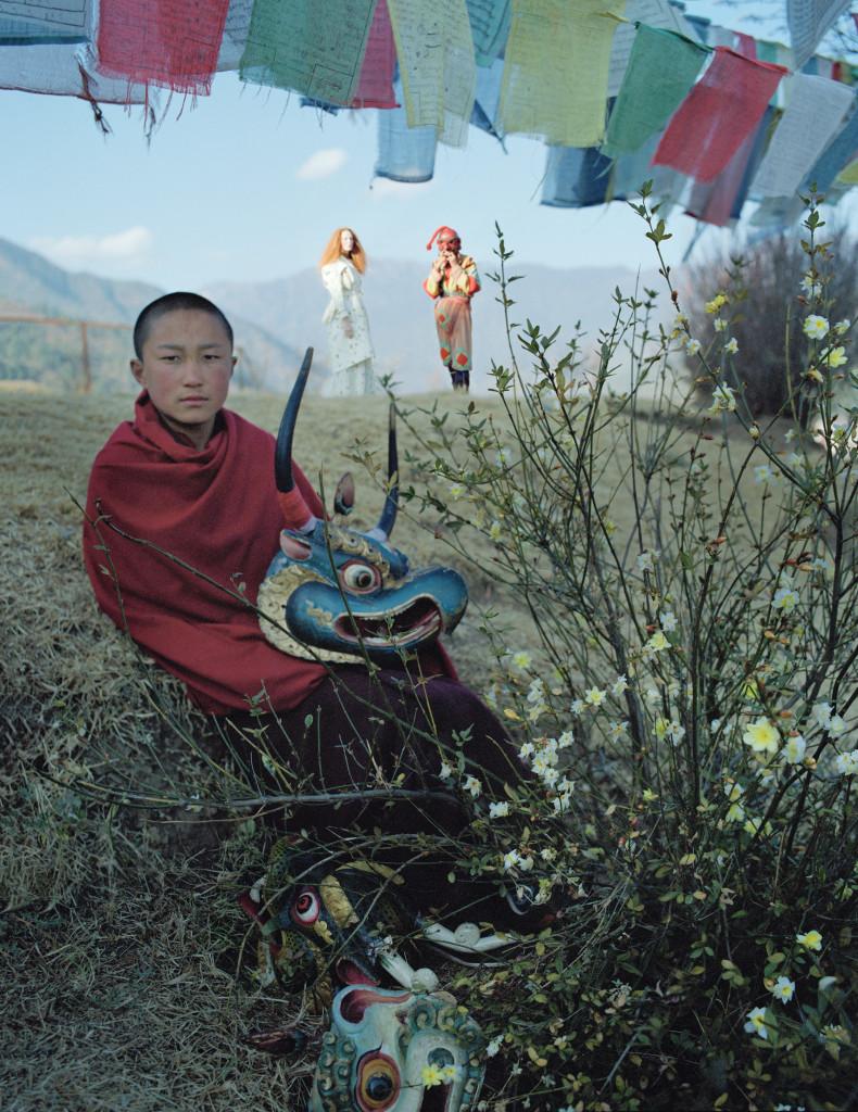 팀푸의 수도원 벽에 걸리게 될 초상화를 위해 포즈를 취한 동자승. 언덕 위의 카렌은 풍요로움과 다산의 상징인 앗사라(Atsara)의 탈을 쓴 스님과 대화를 나누고 있다. 실크 코트와 드레스는 로샤(Rochas).