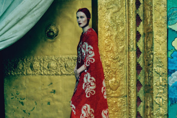 Fashion feature, brocades, silhouettes, silks, feminine, elegant, nature of Bhutan, travel, local, colours, culture, model with red hair, temple, gold, peals, wears tapestry cape with embroidery by Simone Rocha, silk fabric, satin cap by Piers Atkinson