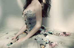 Cover feature, article, interview, couture with Emilia Clarke, portrait, minimal make-up, sitting, wears strapless ballerina dress with embroidered crystals, floral, by Dolce & Gabbana Alta Moda