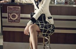 모던한 페이턴트 소재가 칼라와 소매에 덧대진 아이보리색 더블 버튼 재킷과 뜨개실로 격자무늬를 수놓은 페이턴트 스커트는 '뉴 부르주아' 룩을 보여준다.