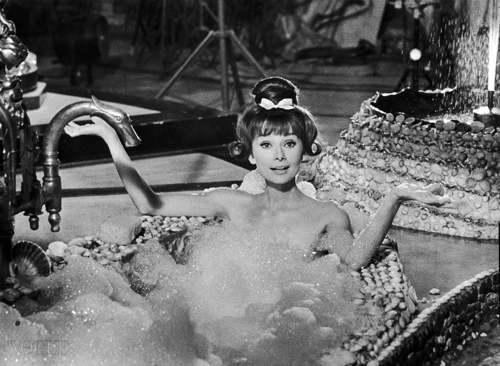 1963:  Belgian-born actor Audrey Hepburn (1929 - 1993) holds her arms out while sitting up to her chest in soap suds in a seashell-lined bathtub, in a still from director Richard Quine's film, 'Paris When It Sizzles.' Hepburn has bangs, long tendrils that flip up on either side, and a bun on top of her head.  (Photo by Paramount Pictures/Getty Images)