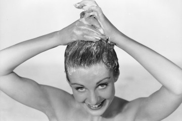 30th June 1952:  A woman applies shampoo to her hair.  (Photo by Chaloner Woods/Getty Images)