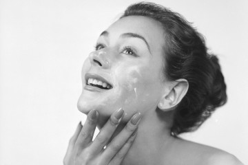 17th June 1952:  A woman applies cream to her face and neck.  (Photo by Chaloner Woods/Getty Images)