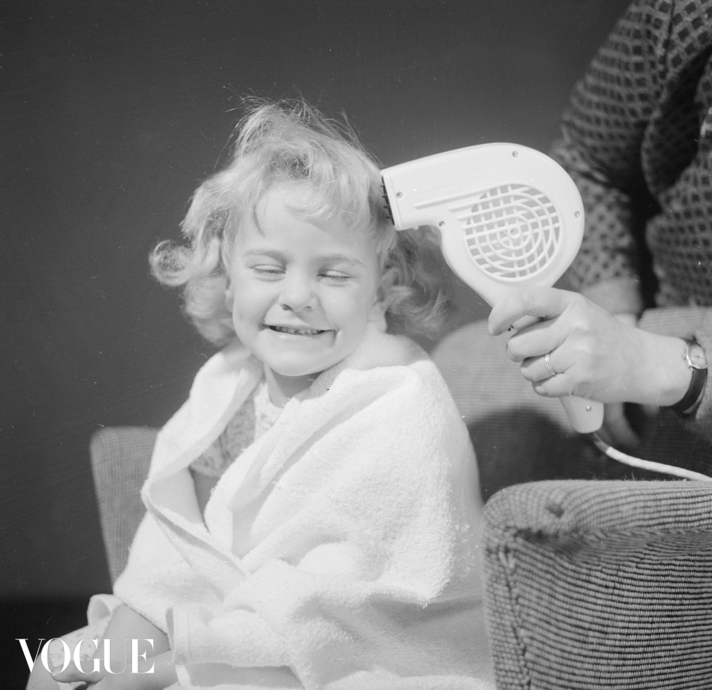 29th October 1959:  Wrapped in a towel, a little girl is having her hair dried with a hand held hair dryer.  Mother - pub. 1959  (Photo by Chaloner Woods/Getty Images)