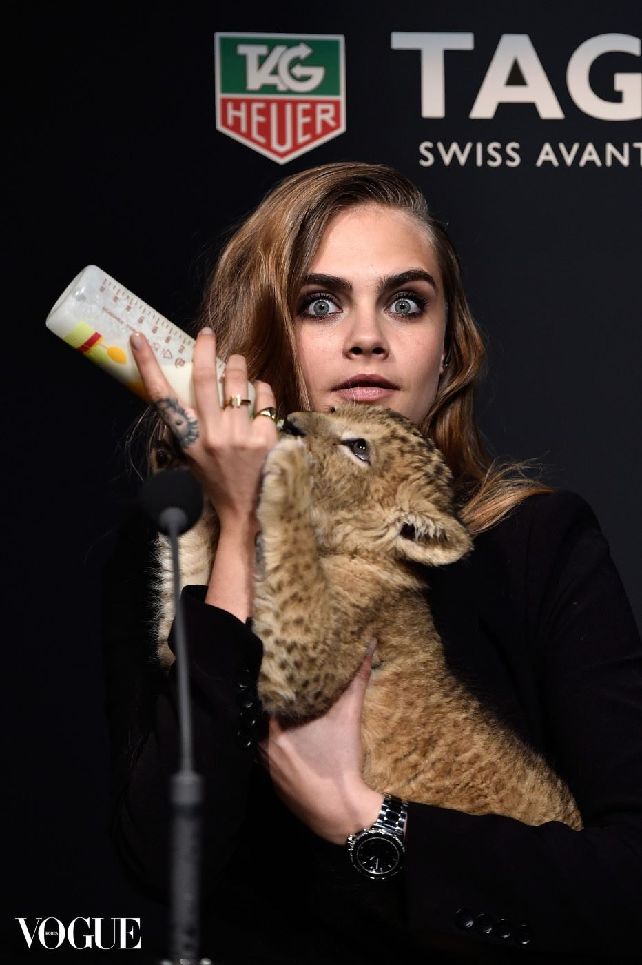 PARIS, FRANCE - JANUARY 23:  Model Cara Delevingne poses with a baby lion as she joins TAG Heuer as Brand Ambassador to launch the new 2015 campaign at Palais des Beaux-Arts on January 23, 2015 in Paris, France.  (Photo by Pascal Le Segretain/Getty Images for TAG Heuer)