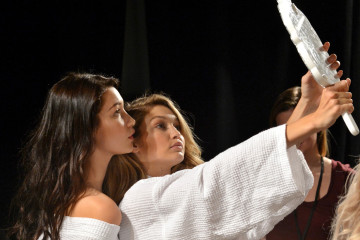 NEW YORK, NY - OCTOBER 20:  Models Gigi Hadid (C) and Bella Hadid prepare backstage at the BALMAIN X H&M Collection Launch at 23 Wall Street on October 20, 2015 in New York City.  (Photo by Slaven Vlasic/Getty Images for H&M)