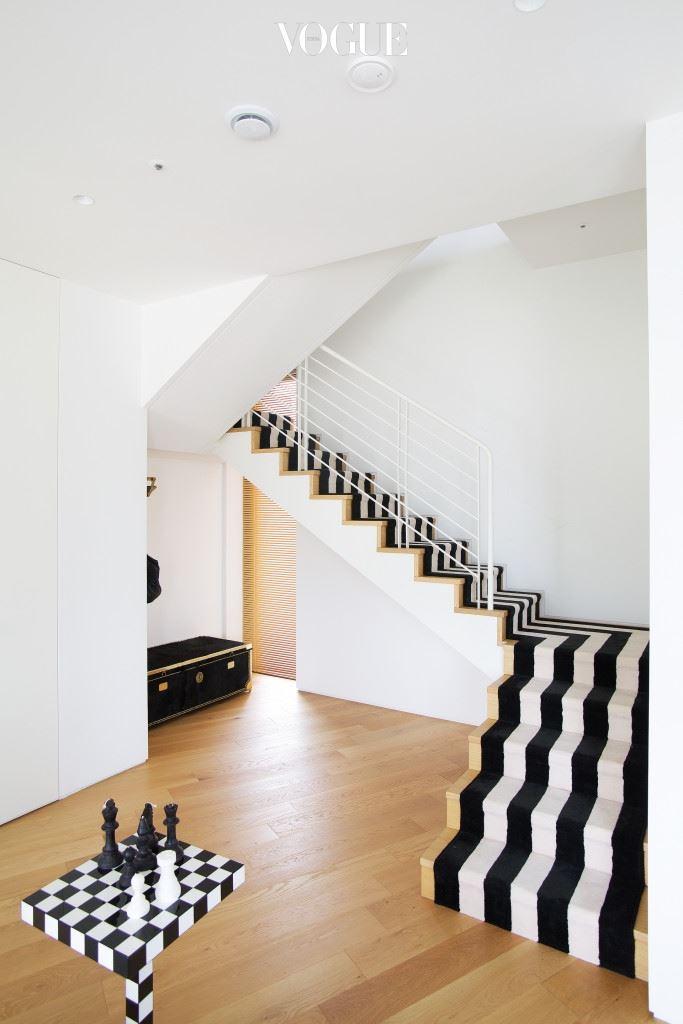 조성아 22의 패키지를 떠올리는 모노크롬 패턴 카펫이 깔린 계단. 그 밑으로 자리한 금궤는 손님들의 짐을 보관하기 위해 만든 수납공간이다.