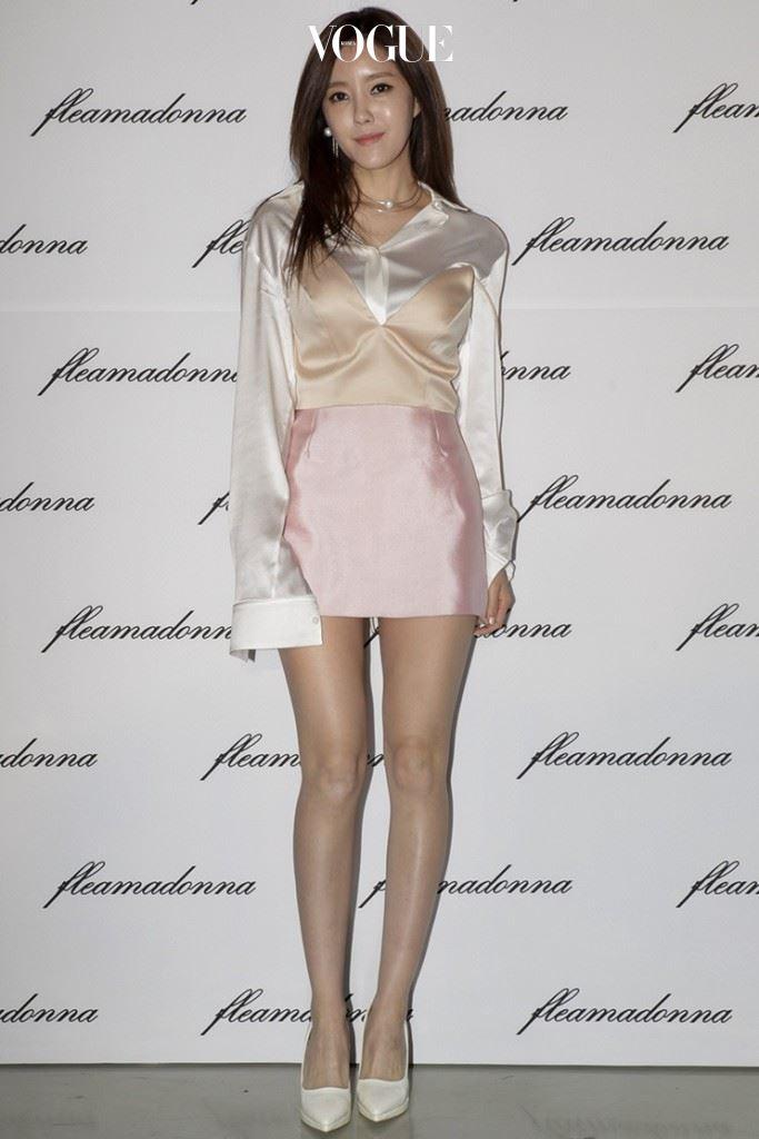 티아라 효민 새틴 소재 블라우스에 살구색과 핑크색이 믹스된 슬립 드레스를 레이어링한 뒤 진주 주얼리와 하얀색 플랫폼 슈즈를 매치해 여성미를 어필했다. 프리마돈나(FLEAMADONNA)
