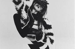 스트라이프 프린트의 프린지 스웨터에 미디 스커트를 입은 룩과 검정 보디수트와 가죽 장갑의 위트 넘치는 신.