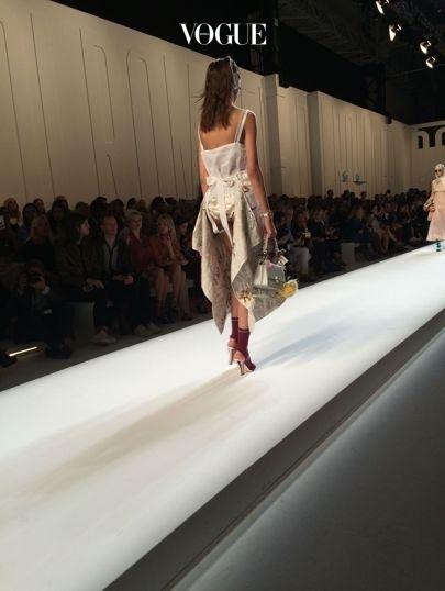 속바지가 살짝 보이는 새틴 에이프런 드레스의 뒷모습.