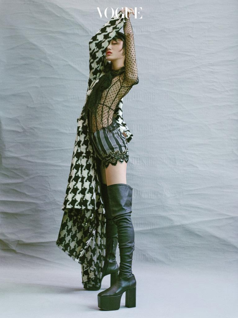 비즈가 박힌 셰퍼드 체크 코트는 돌체앤가바나(Dolce&Gabbana), 시스루 셔츠와 줄무늬 실크 쇼츠는 마크 제이콥스(Marc Jacobs), 블랙 플랫폼 힐은 발렌시아가(Balenciaga).