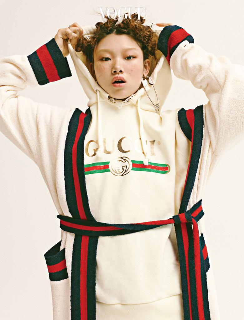 큼지막한 니트 카디건과 로고 후디는 구찌(Gucci), 옷핀 모양 귀고리는 발렌시아가(Balenciaga).
