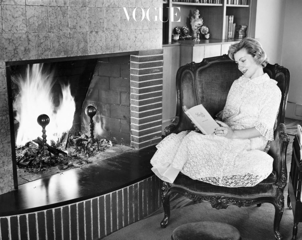 Young woman sitting by fireplace reading book
