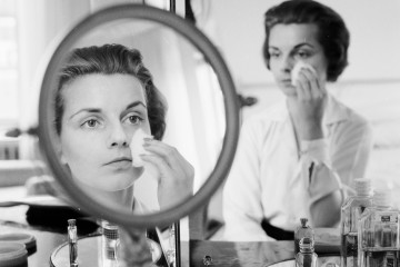 circa 1955:  A woman rubbing her face with cotton wool to remove make up or apply moisturiser.  (Photo by Jacobsen /Three Lions/Getty Images)