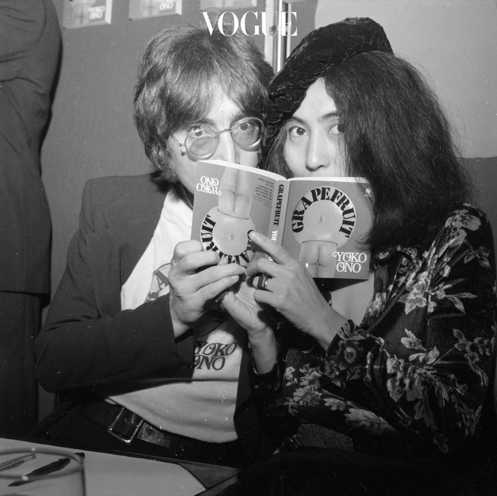 15th July 1971:  Japanese-born artist Yoko Ono and her husband, singer and songwriter John Lennon (1940 - 1980), posing behind a copy of Ono's newly-published photography book 'Grapefruit' at a book signing session at Selfridge's department store, London.  (Photo by Central Press/Getty Images)