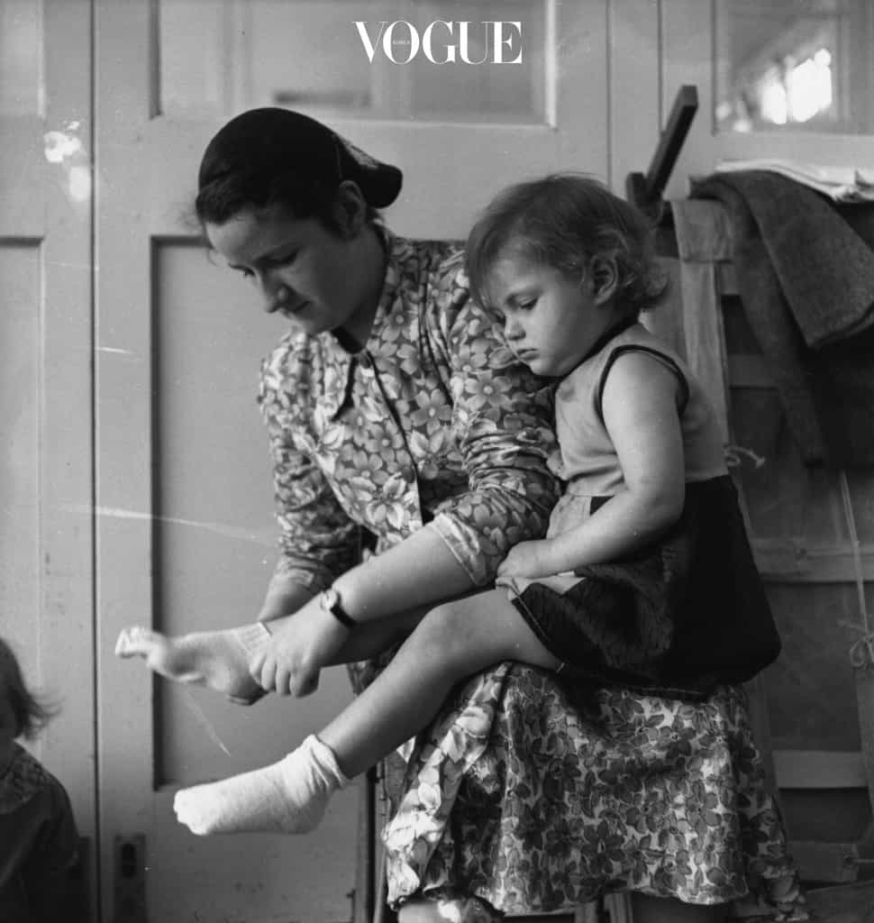 circa 1950:  A day nursery staff member puts on a little girl's socks and shoes as her mother will soon be there to fetch her.  (Photo by Keystone/Getty Images)
