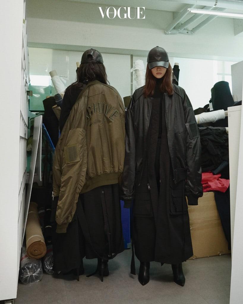 준지의 아이코닉한 오버사이즈 트렌치 코트와 MA-1 재킷을 입고 준지 사무실의 원단 더미 앞에서 포즈를 취했다. 의상과 액세서리는 2017 F/W 컬렉션.