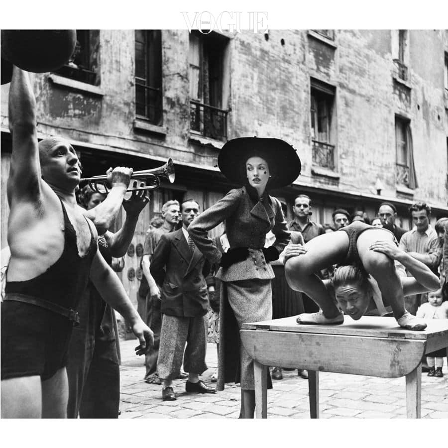 Elise Daniels with street performers, Le Marais, Paris, 1948. Suit by Balenciaga